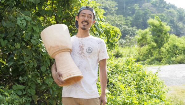 自作したジャンベを持ち、笑う木村さん。作成した後、木を乾燥させて太鼓は完成する。