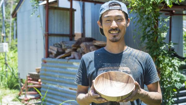 工房の前で小笠原の樹を使った自作の器を持って笑う木村さん。