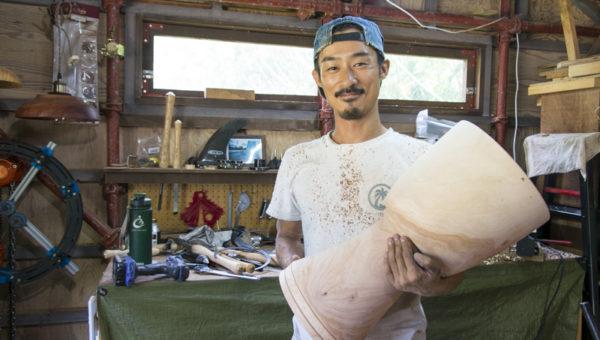 完成したジャンベを持ち、笑う木村さん。作成した後、太鼓を乾燥させて太鼓は完成する。